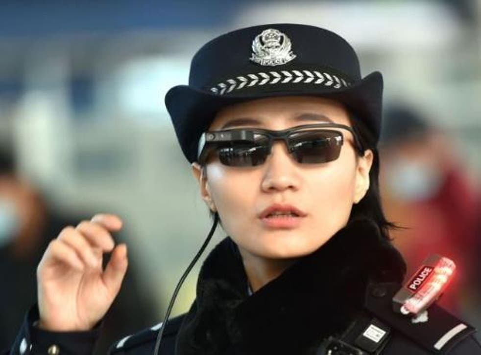 This photo taken on 5 February 2018 shows a police officer wearing a pair of smart glasses with a facial recognition system at Zhengzhou East Railway Station in Zhengzhou in China's central Henan province
