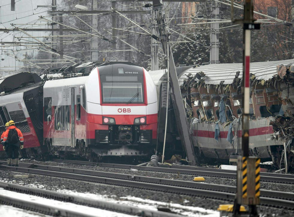 Rescuers at the site where two passenger trains collided in Niklasdorf, central Austria.