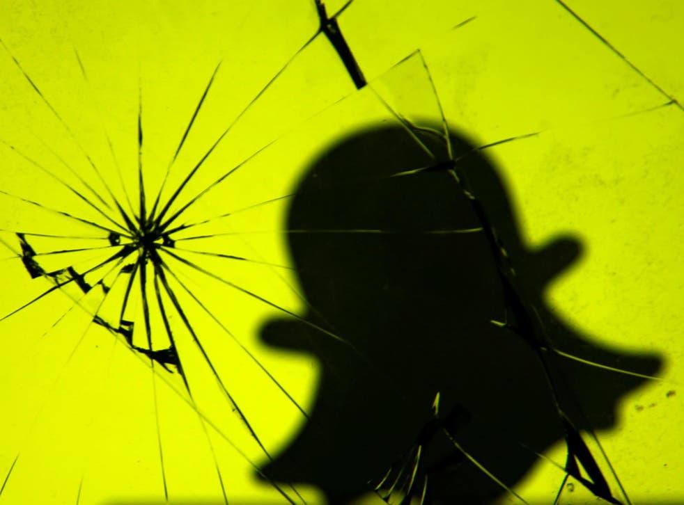 A 3D printed Snapchat logo is seen through broken glass in this illustration taken November 7, 2017