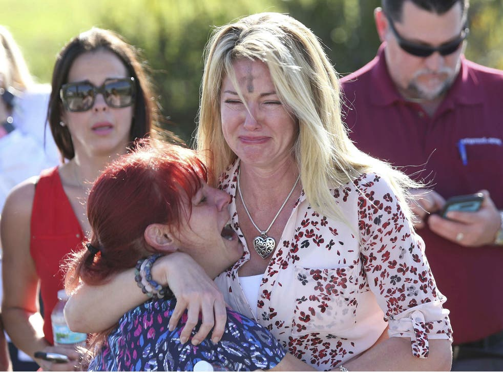 Parents wait for news after a shooting at Marjory Stoneman Douglas High School in Parkland, Florida