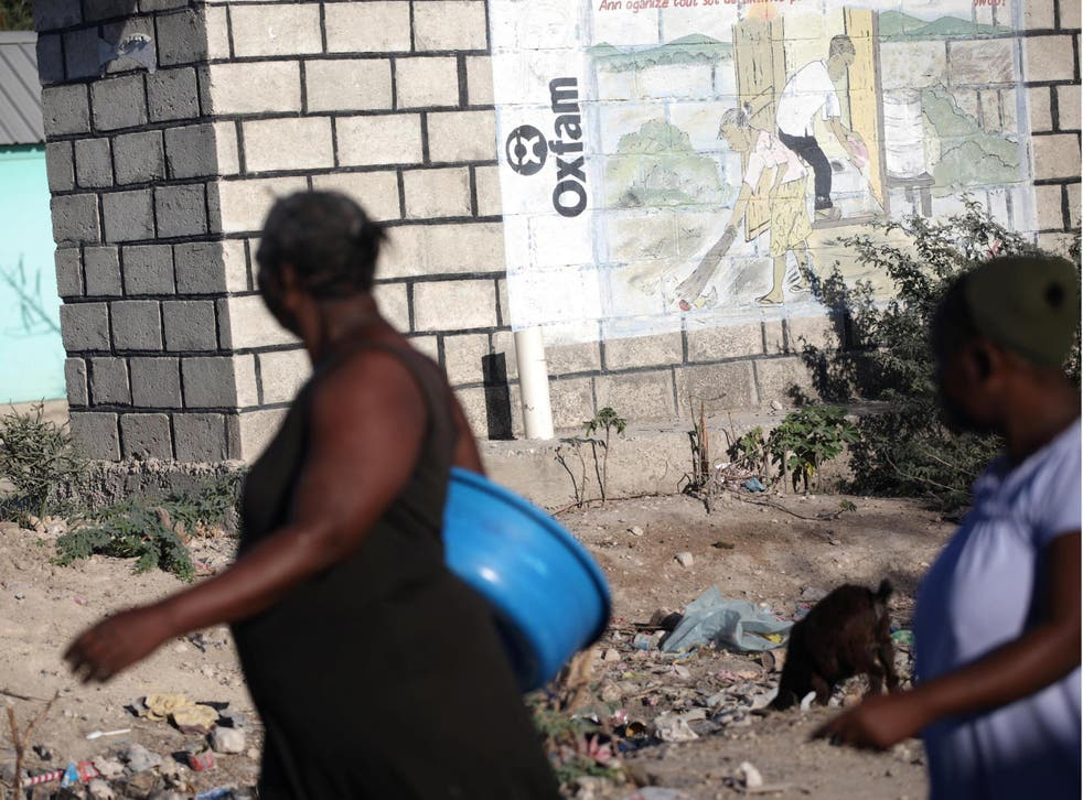 People walk past an Oxfam sign in Corail, a camp for people displaced after 2010 earthquake, on the outskirts of Port-au-Prince, Haiti