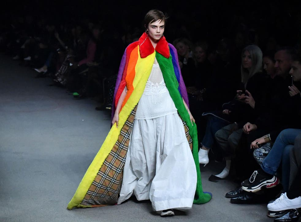 Cara Delevingne presents a Burberry creation during the brand's catwalk show