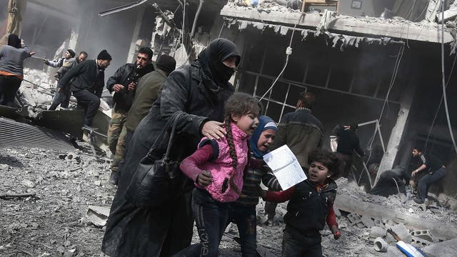 A Syrian woman and children run for cover amid the rubble of buildings.