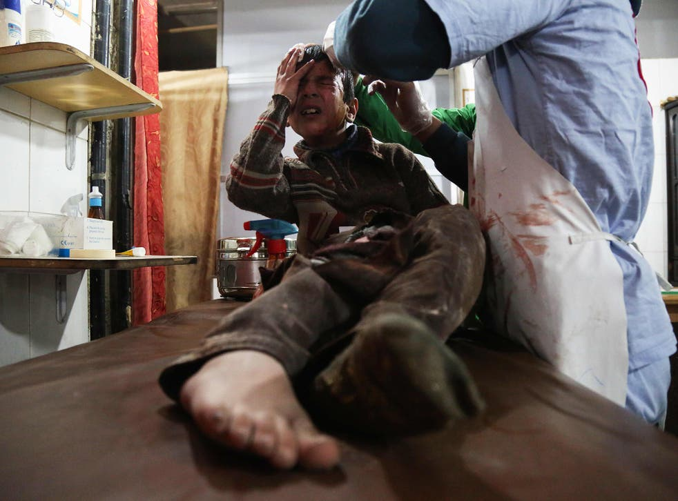 A wounded 12-year-old Syrian boy, cries as he receives treatment at a makeshift hospital on Monday