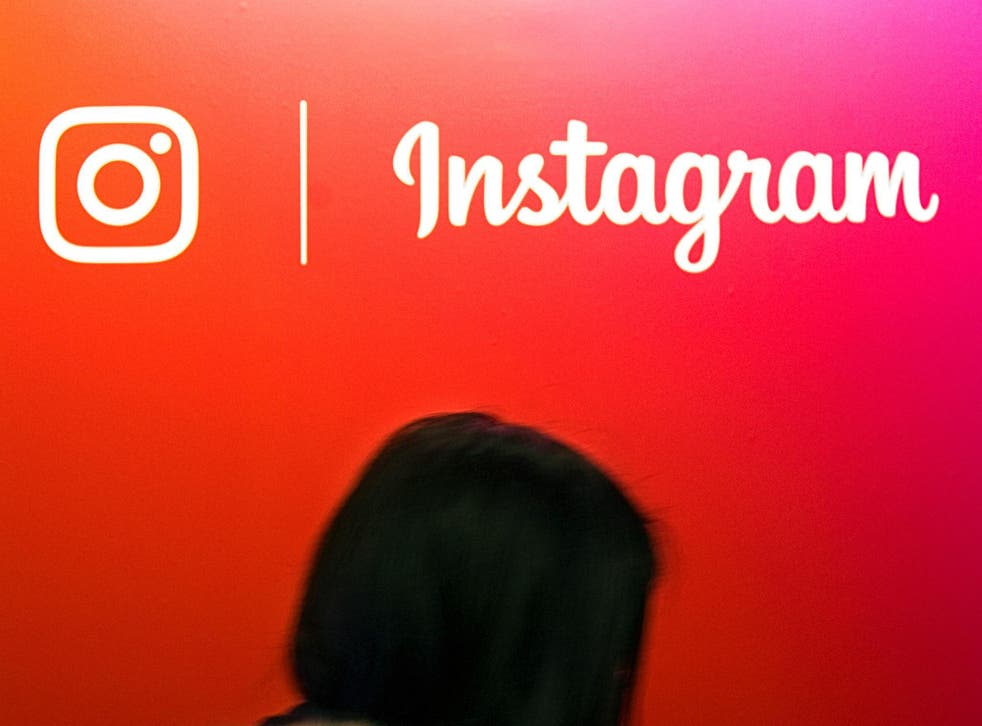 A visitor passes by the Instagram application logo at the Young Entrepreneurs fair in Paris, France, February 7, 2018