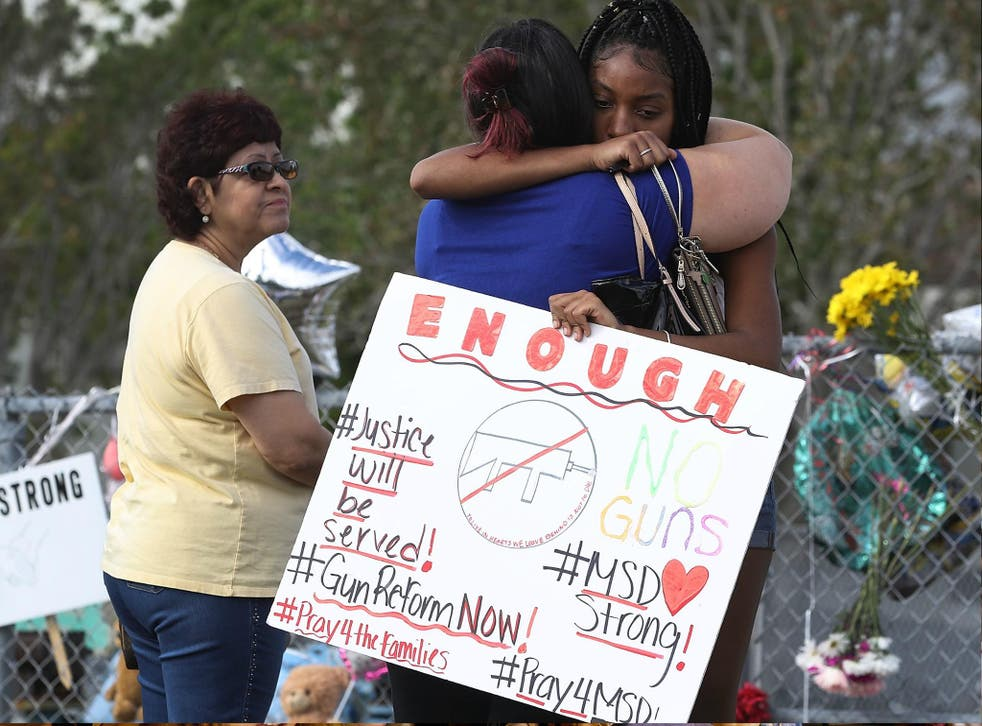 Tyra Heman, a senior at Marjory Stoneman Douglas High School, holds a sign that reads, 'Enough No Guns,' on 19 February 2018 in Parkland, Florida.