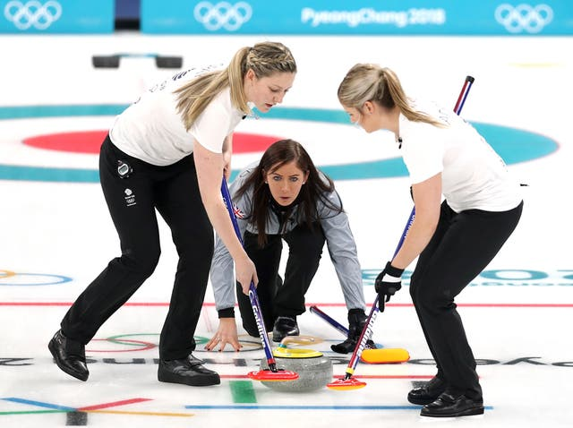 Lauren Gray, left, and Vicki Adams sweep the ice in front of a stone cast by Eve Muirhead