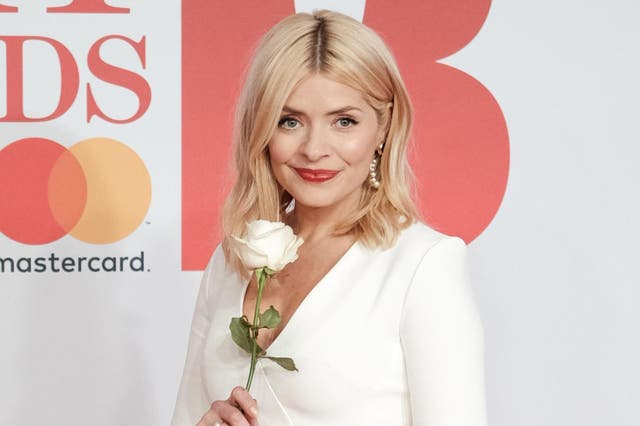 Holly Willoughby appearing on the red carpet at the Brit Awards carrying a white rose as a symbol of the Time's Up movement