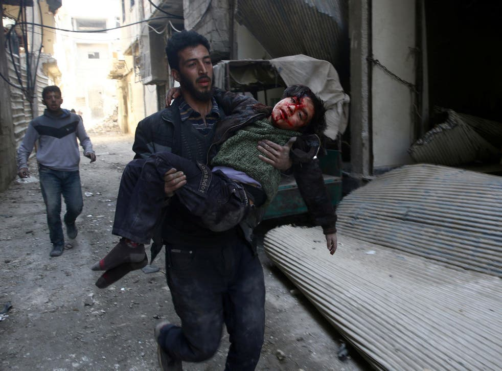 Mohammed Abu Anas runs with an injured boy in the besieged eastern Ghouta town of Hamouriyeh near Damascus, Syria, on 21 February 2018