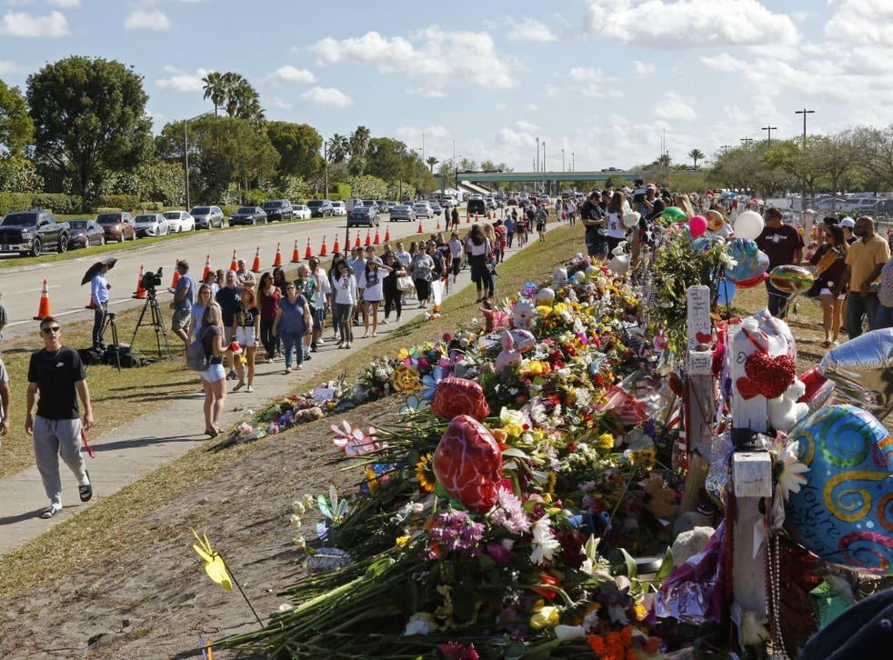 Parents and students walk by the memorial for the victims of the shooting at Marjory Stoneman Douglas High School on the way to open day