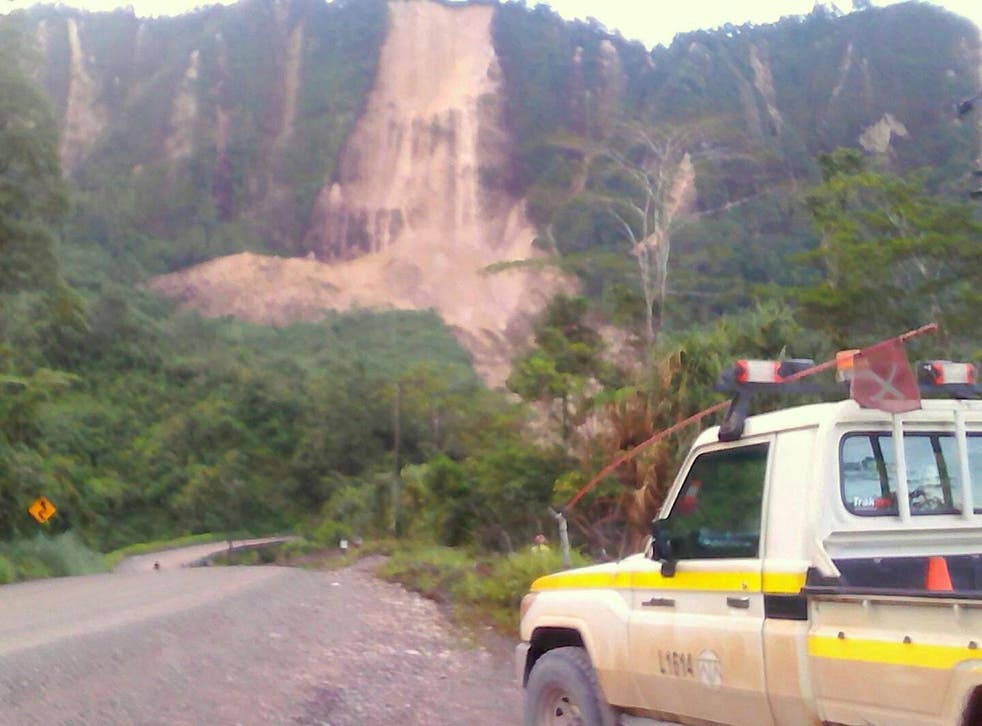 Locals near Tabubil inspect a landslide and damage to a road after a major earthquake struck Papua New Guinea's Southern Highlands