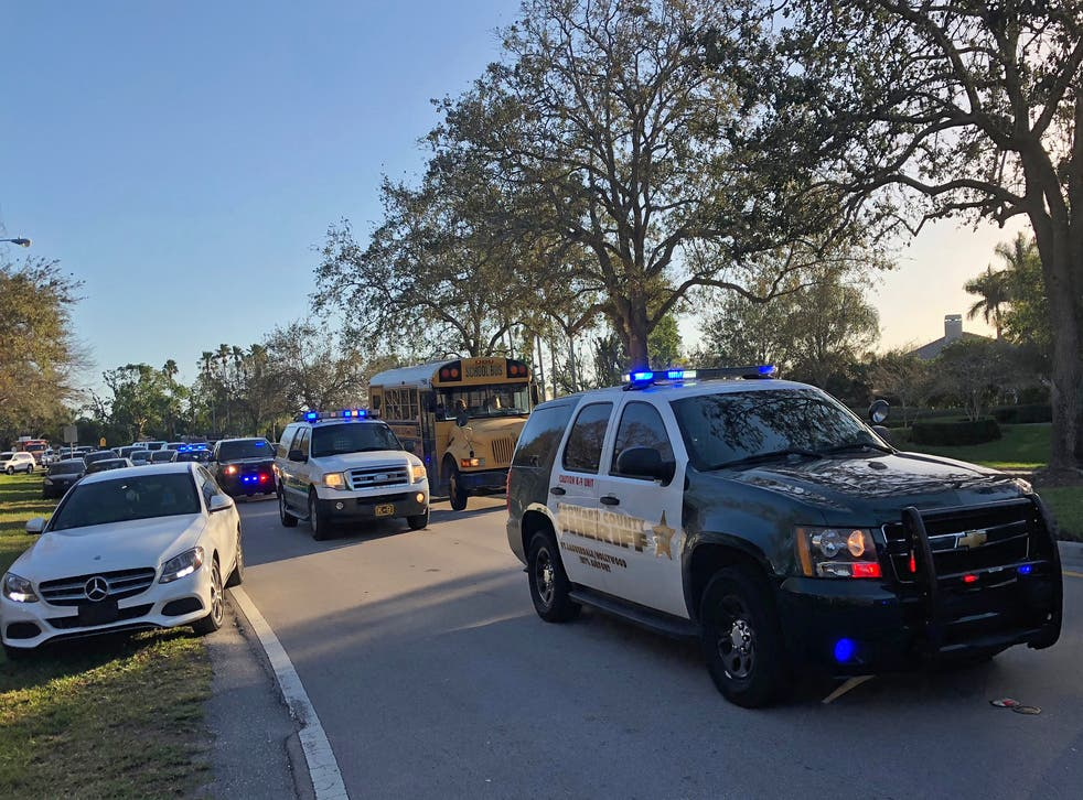 Police and security vehicles are seen at Marjory Stoneman Douglas High School in Parkland, Florida, following a school shooting