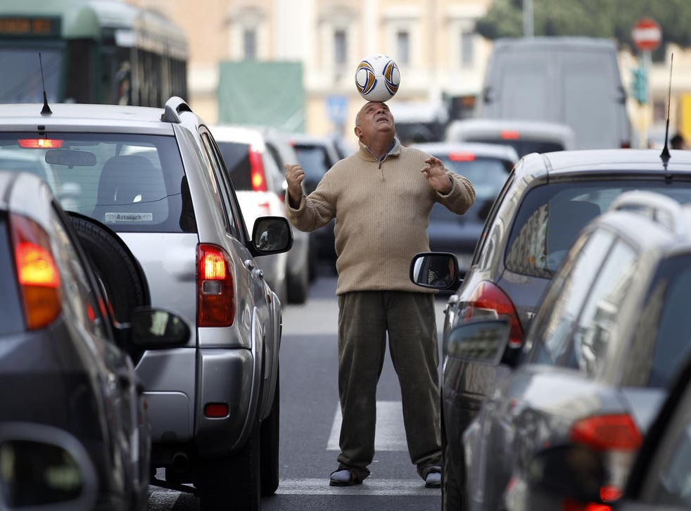 A man balances a soccer ball on his head amongst cars stopped in a traffic jam in Rome April 4, 2012