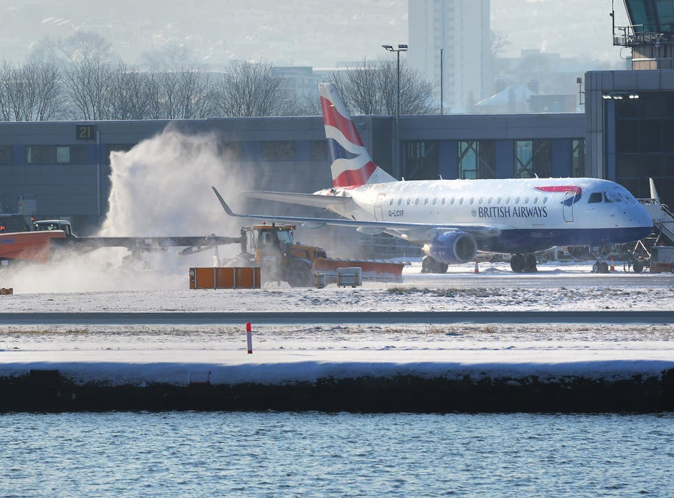 A British Airways passenger plane gets de-iced at London City airport in sub-zero temperatures after an overnight snow storm caused travel chaos across the capital