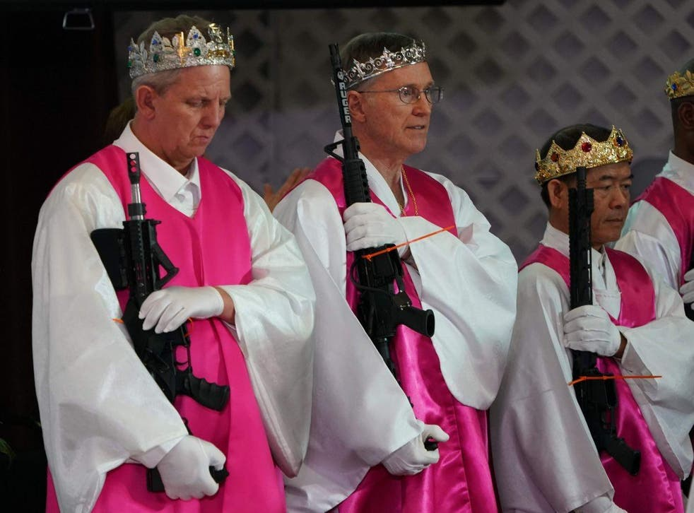Congregants at World Peace and Unification Sanctuary hold weapons during their service