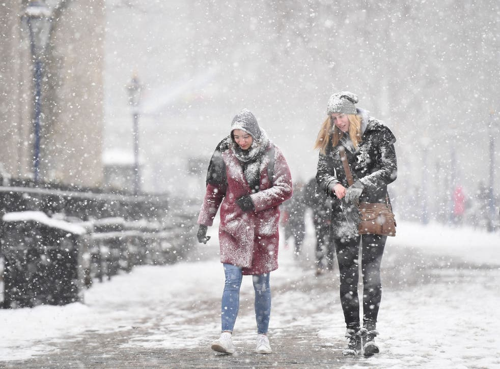 People walking in the snow by Tower Bridge in London, as the highest level of weather warning has been issued for parts of England and Wales