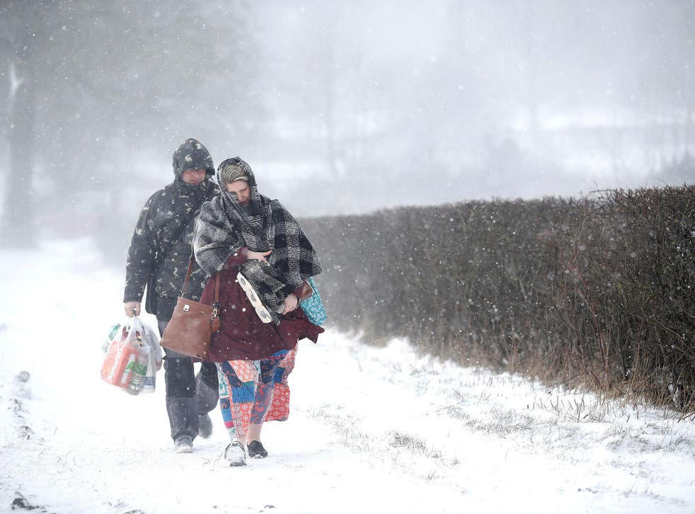 A couple walk along the A53 Buxton Road, which is closed due to heavy snow fall, after abandoning their car near Leek
