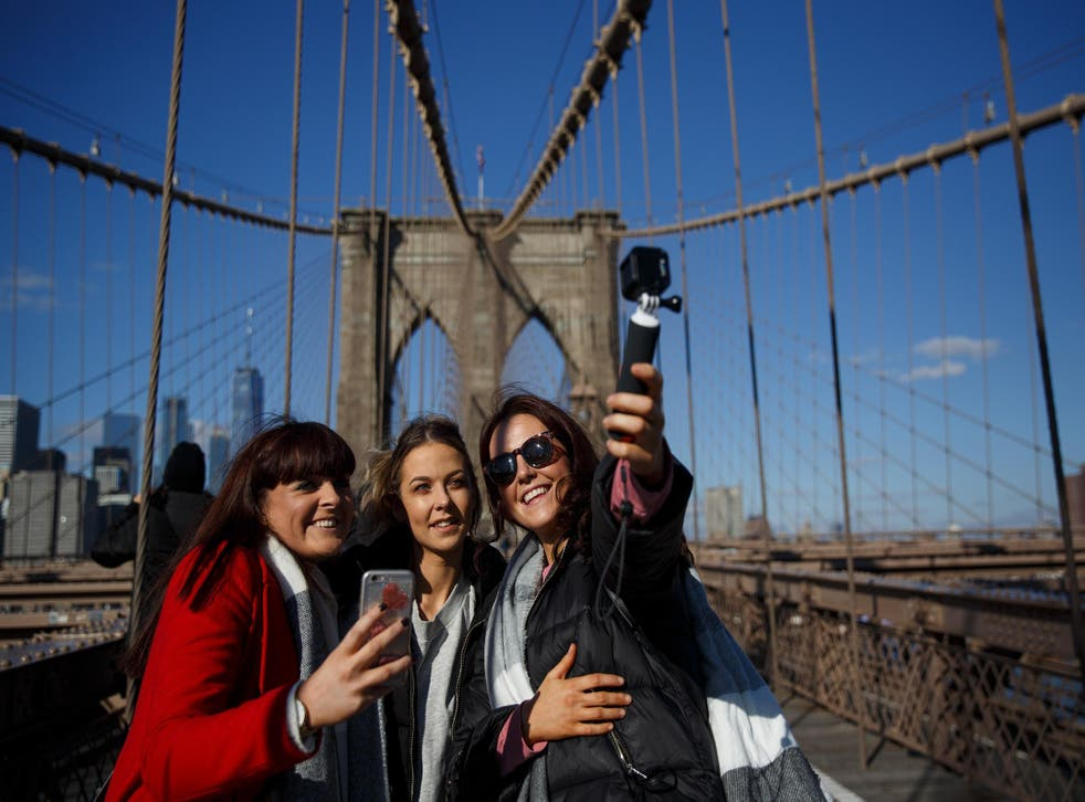 A group of friends takes a photograph on the Brooklyn Bridge