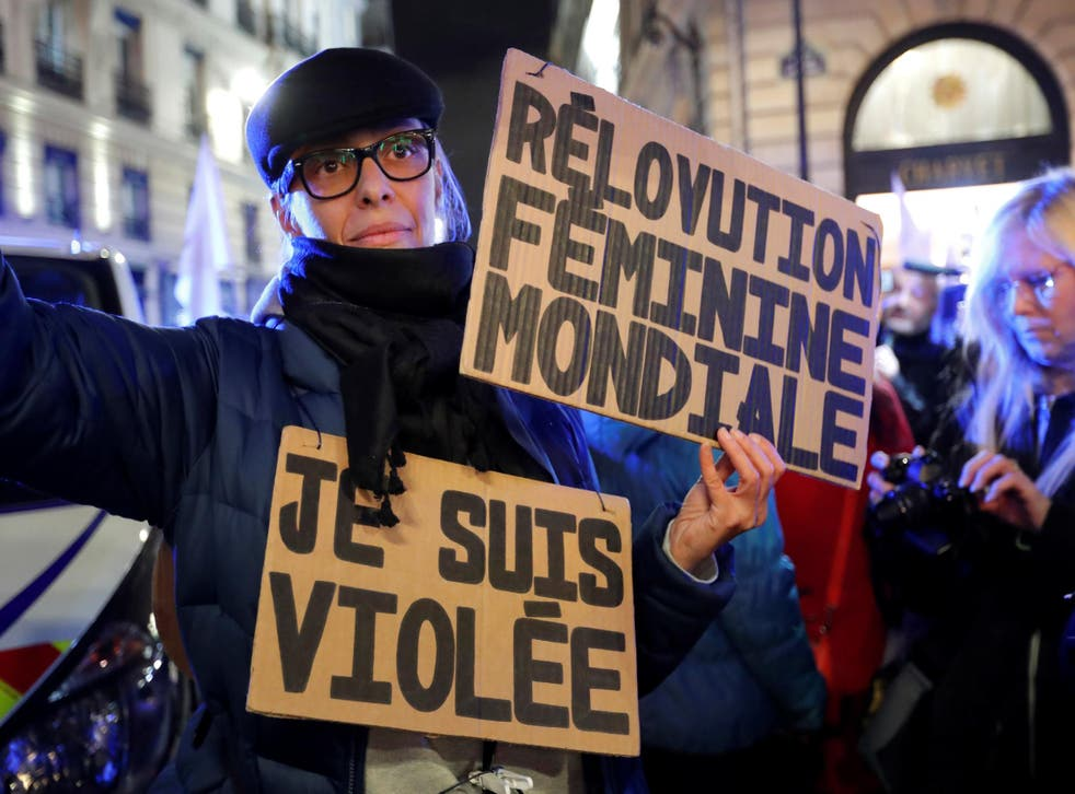 A feminist activist holds placards near the Justice ministry during a protest calling to change French statutory rape laws