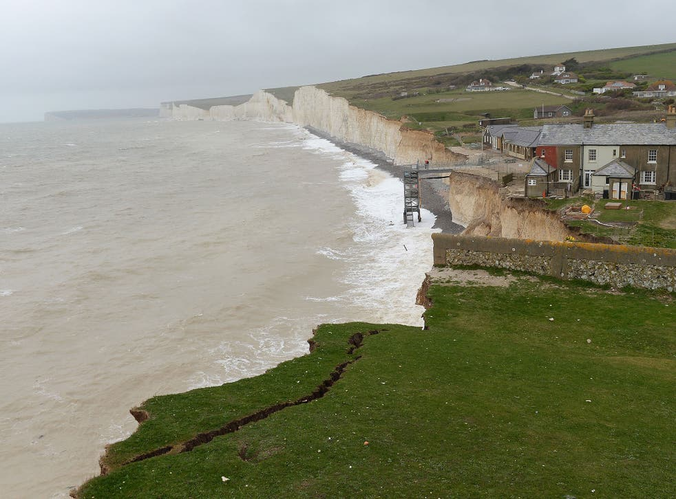 The woman's husband and two young boys were found dead at Birling Gap near Eastbourne