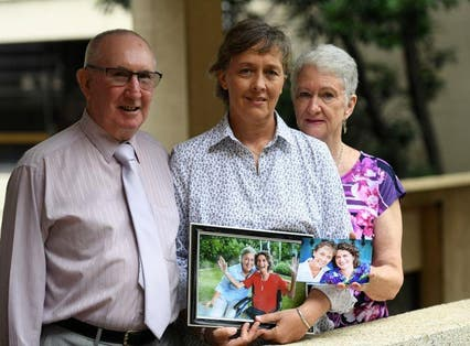Jill Kindt holds a photo of her with her late wife Jo Grant, joined by Jo's mother Sandra Kelly and her husband Paul