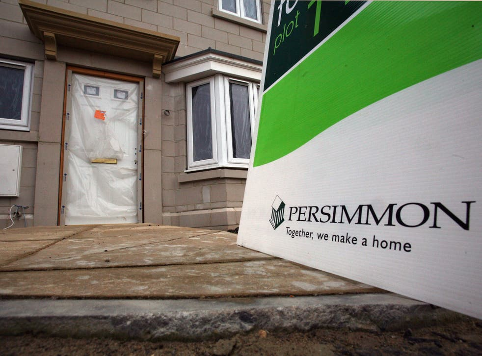 A 'for sale' sign is displayed outside a new build house on a housing estate by developer and housebuilder Persimmon