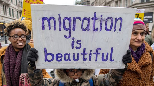 A young boy holds a placard reading 'migration is beautiful' during the march against racism demonstration in London.