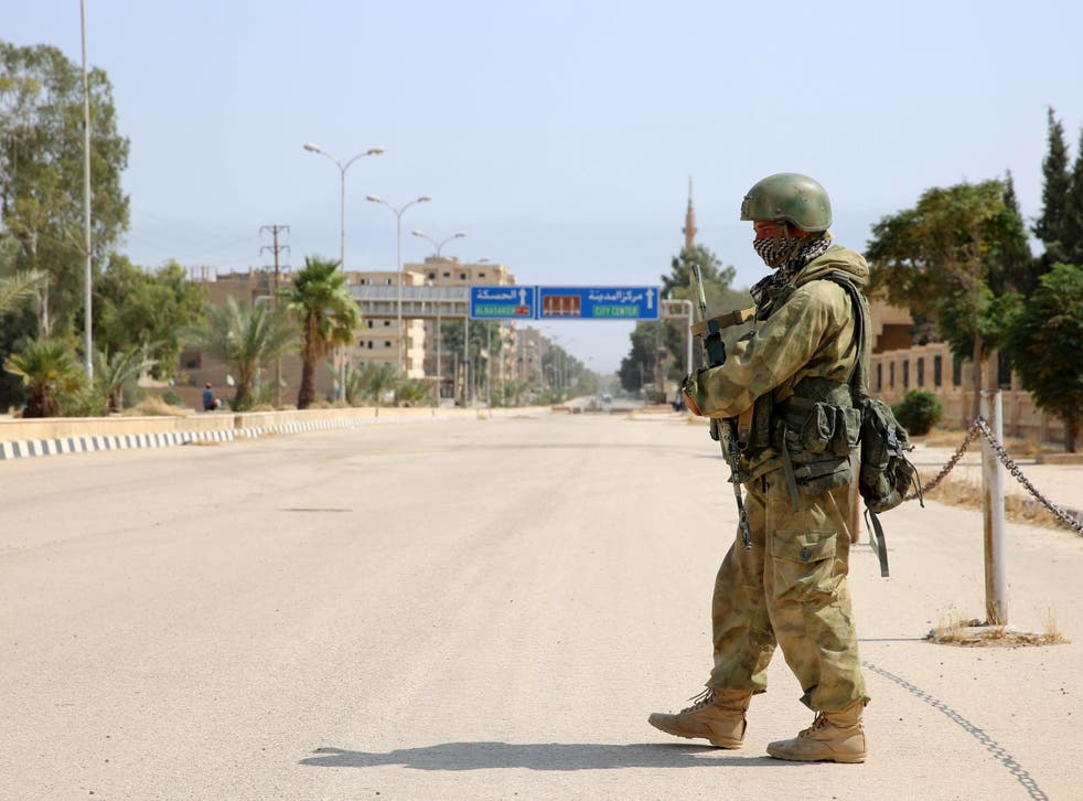 A Russian soldier stands guard in a central street in Syria's eastern city of Deir Ezzor
