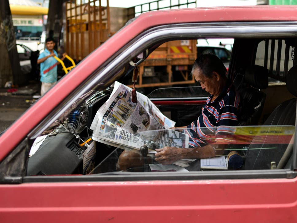 Malaysia plans to make fake news punishable up to 10 years in prison a malaysian man with a newspaper on his lap inside his minivan at a wet market fandeluxe Image collections