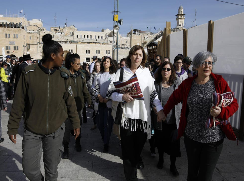Women of the Wall protesters are escorted by border police during a demonstration by ultra-Orthodox Jewish men against the group in Jerusalem's Old City, 27 February 2017