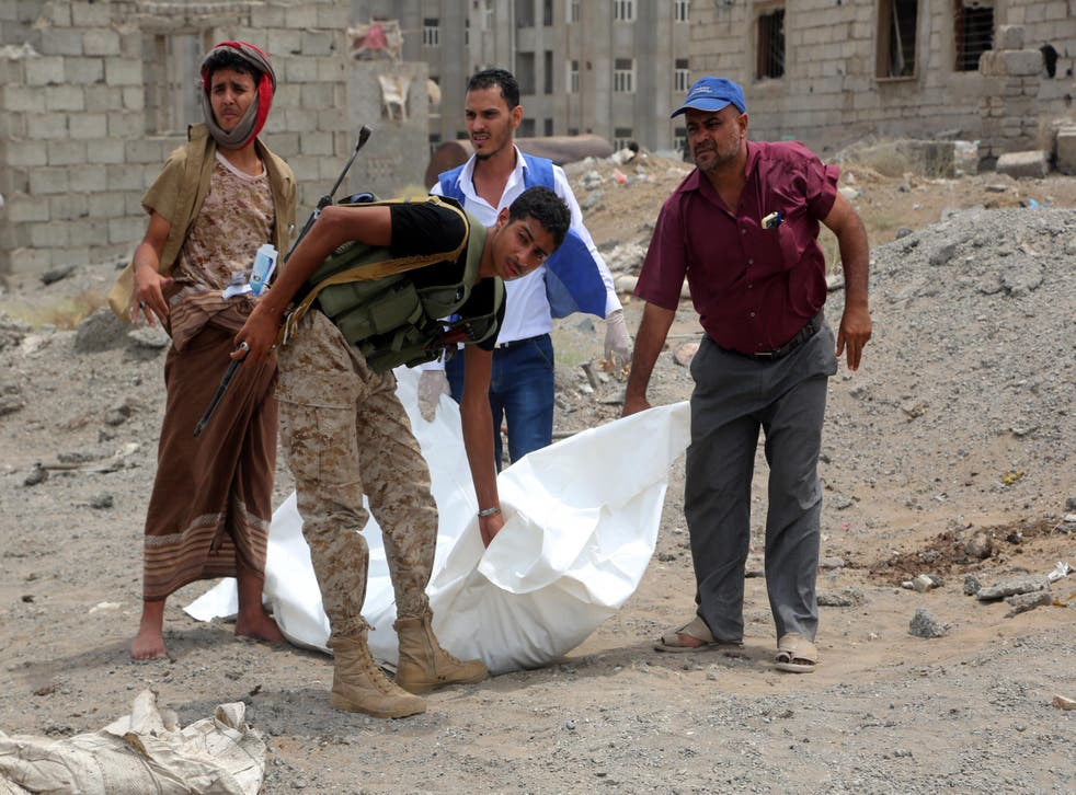Men carry the body of a victim who was killed in an air strike in the district of Al-Hali in Hodeida province, Yemen, on 2 April 2018