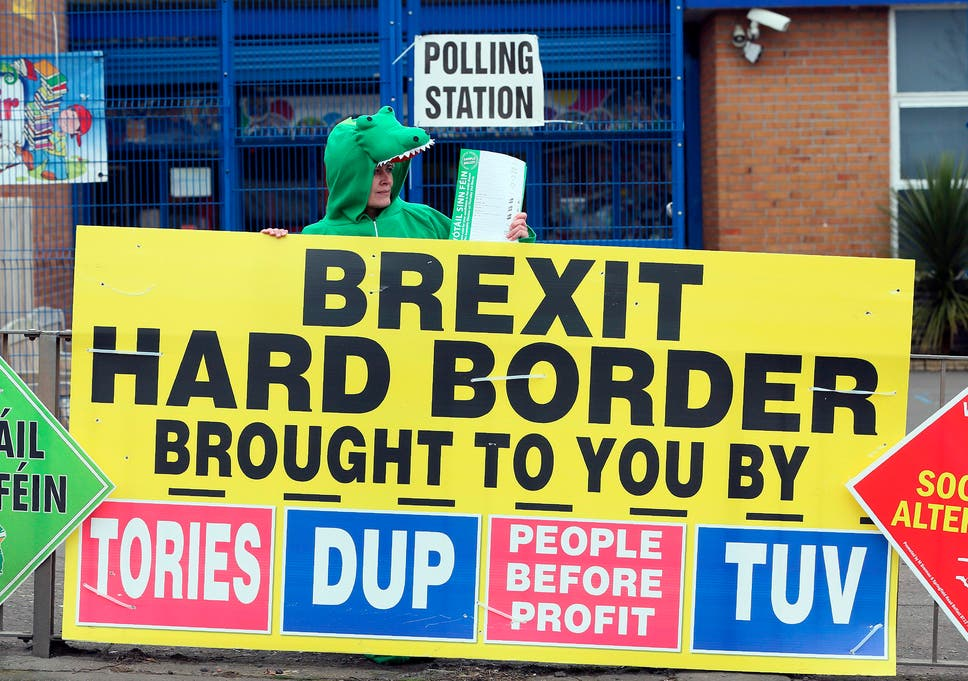 A Sinn Fein party election worker dressed up as a crocodile stands behind a banner referring to Brexit outside a polling station in Belfast