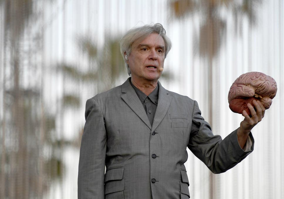 david byrne opens coachella set sitting at a table holding up a