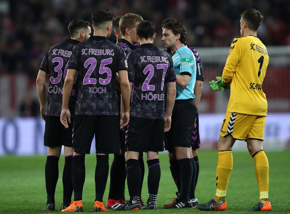 Referee Guido Winkmann is confronted after ordering the players back onto the pitch