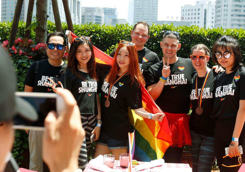 A group poses for photos after taking part in the Pride Run in Shanghai in  June