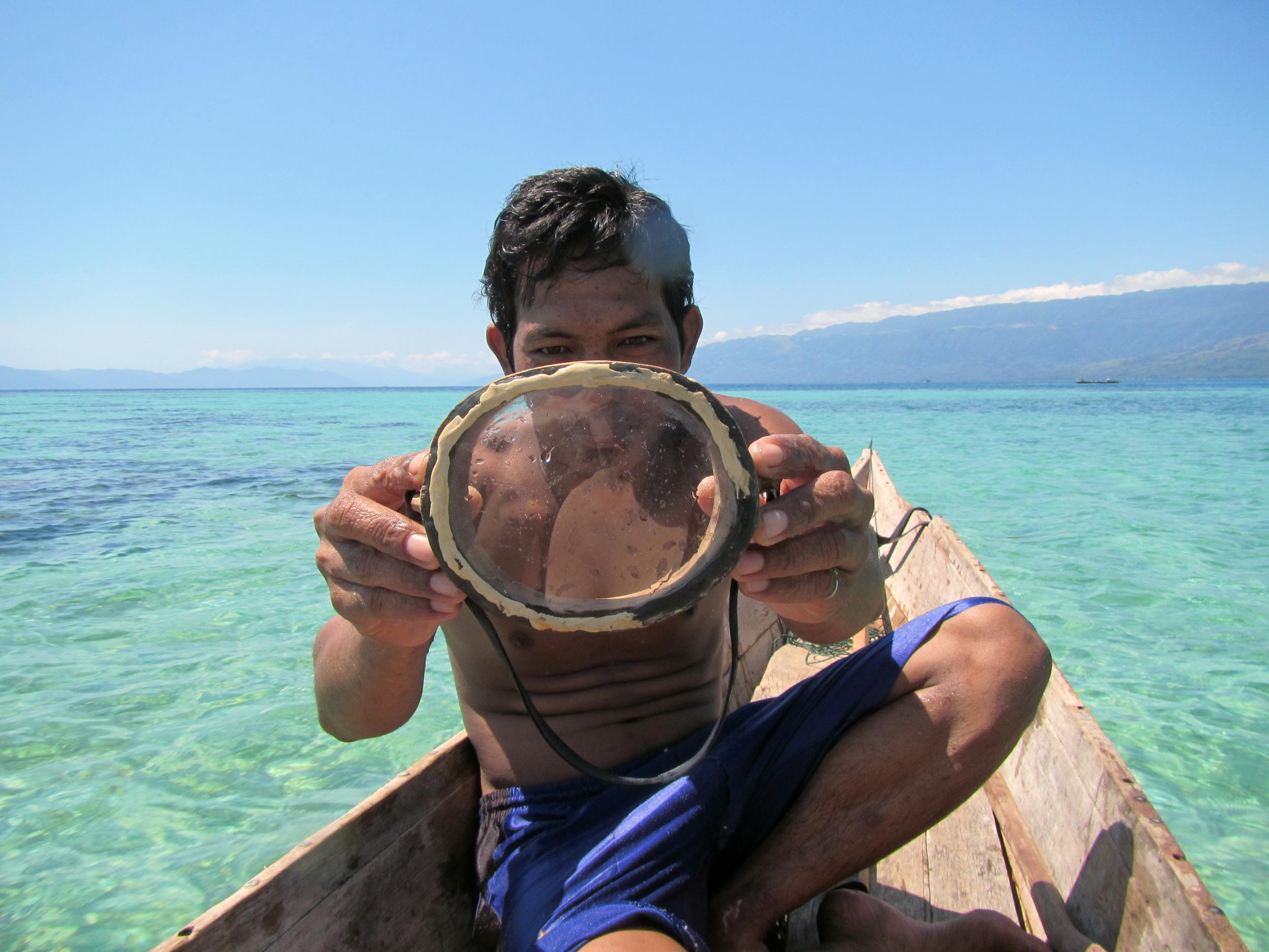 A Bajau diver displays a traditional wooden diving mask