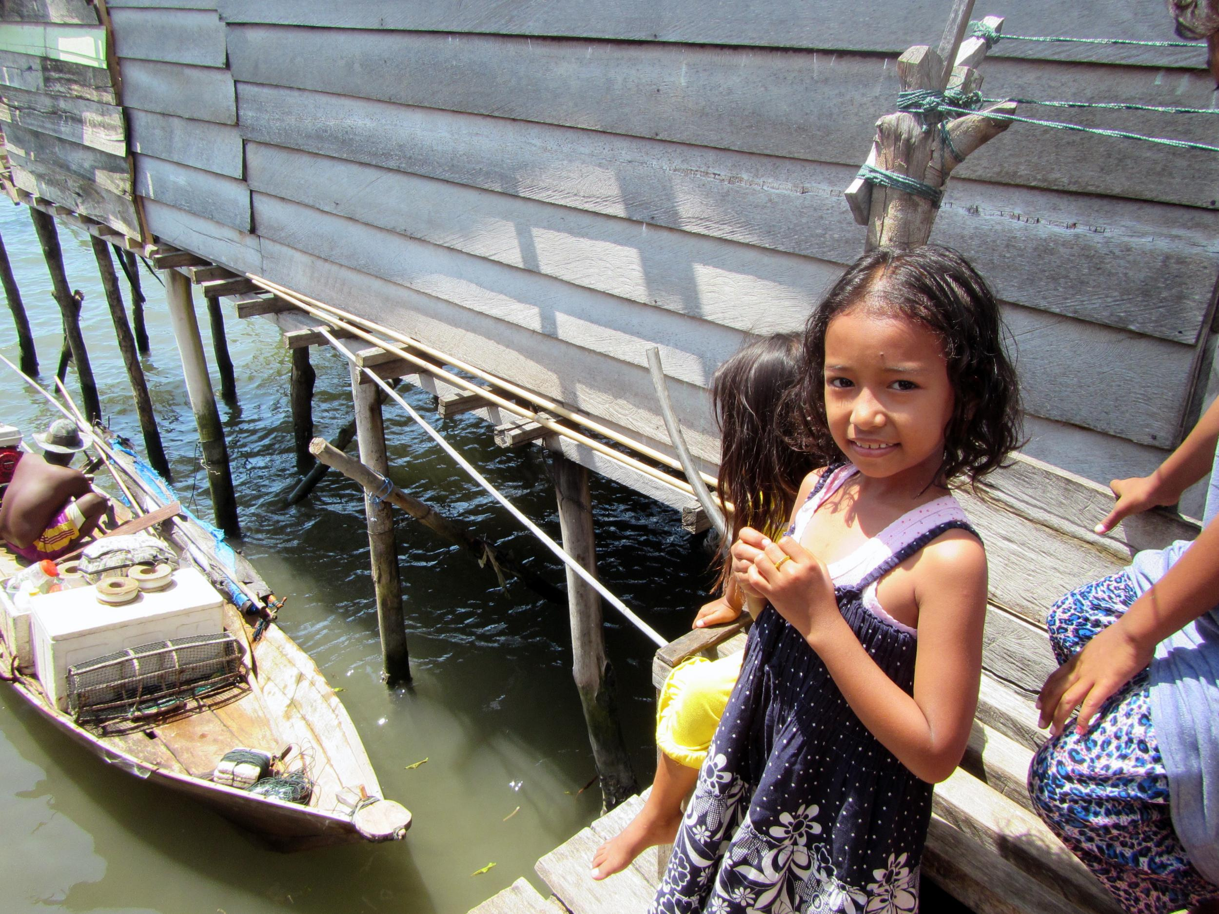 A young Bajau girl looks on in excitement as her father, a traditional Bajau diver, returns to Jaya Bakti from a two-week fishing trip