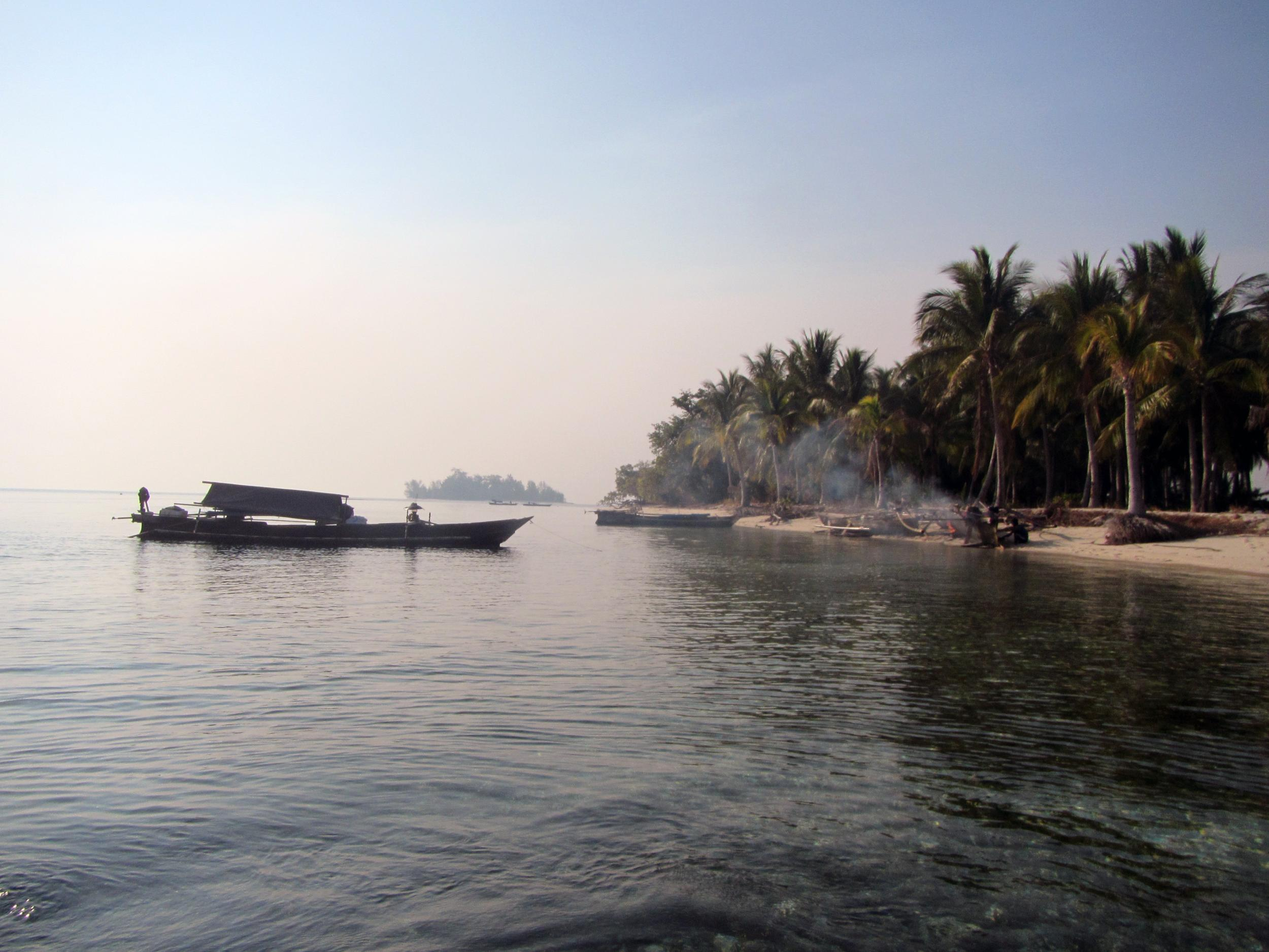 A small, unnamed island serves as a haven for visiting Bajau houseboats