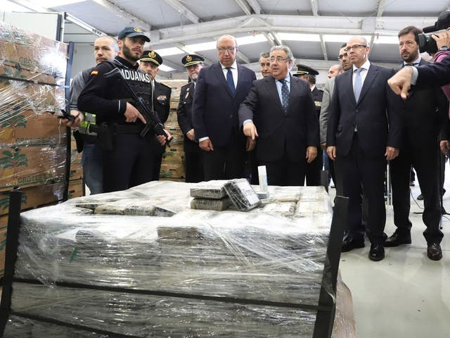 Spain's interoir minister, Juan Ignacio Zoido, stands next to the almost nine tons cocaine shipment seized inside a bananas container at Algeciras port in Cadiz, southern Spain