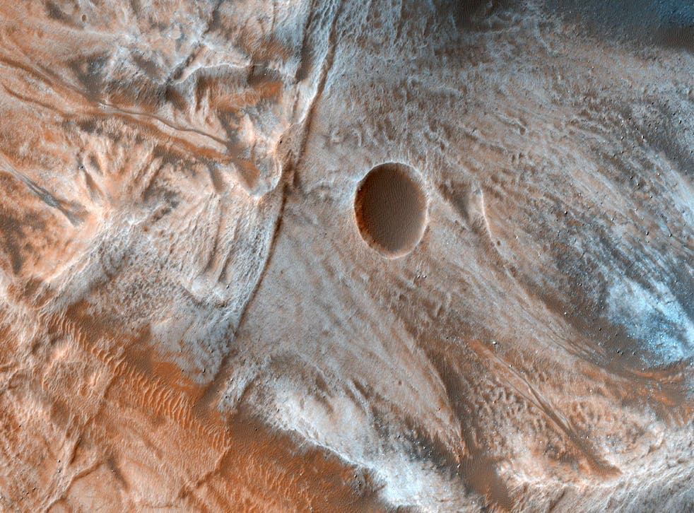 A view of the surface of Mars released by NASA on March 7, 2017, shows viscous, lobate flow features commonly found at the bases of slopes in the mid-latitudes of Mars, and are often associated with gullies