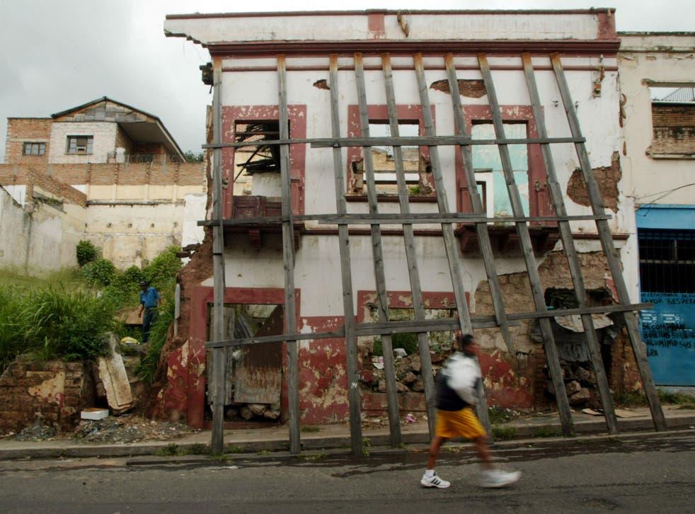 A resident walks past a building destroyed by Hurricane Mitch in Tegucigalpa, Honduras