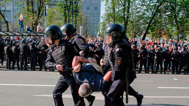 Russian police officers detain a protester in Moscow