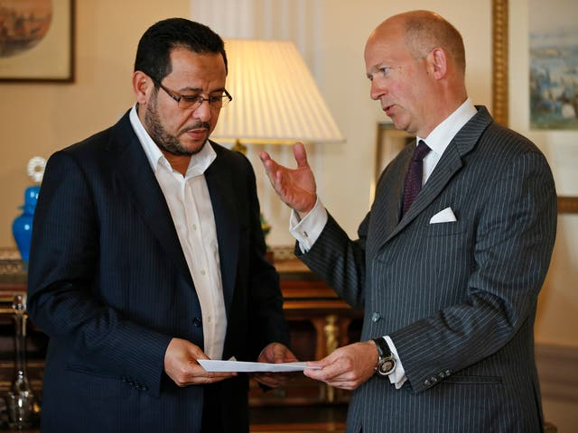 Dominick Chilcott, right, British ambassador in Turkey, hands over a letter of apology from the UK government to Libyan dissident Abdel Hakim Belhaj,  at the British Consulate, in Istanbul