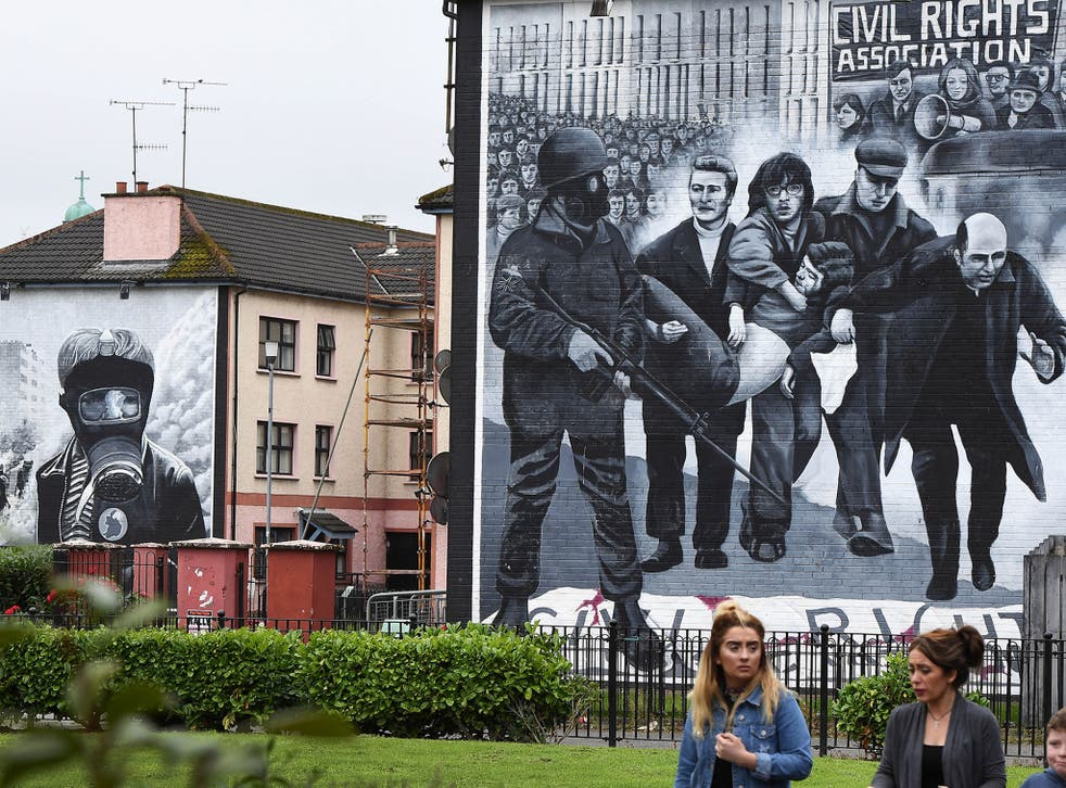 A family walks past a mural depicting a scene from Bloody Sunday