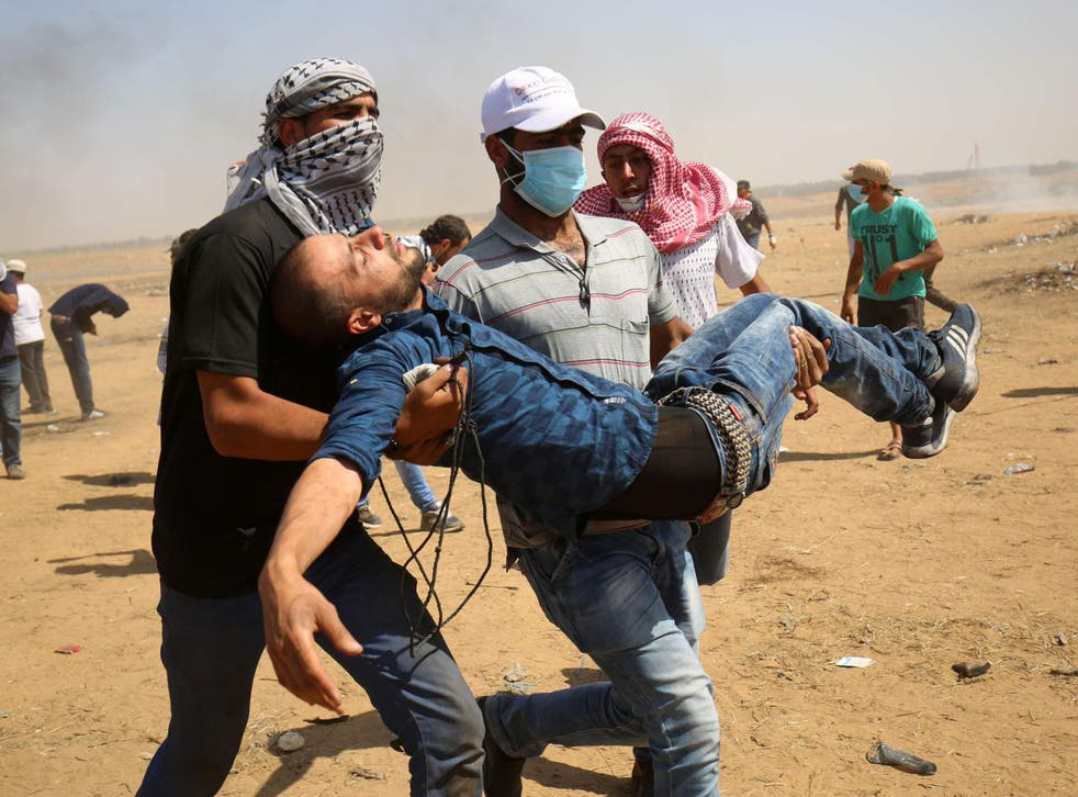 A wounded Palestinian is evacuated during clashes with Israeli forces along the border with the Gaza strip