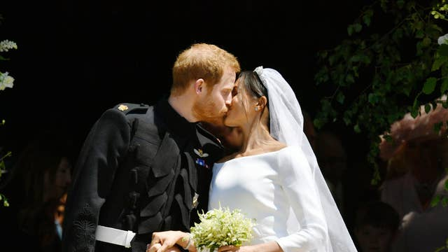 The Duke and Duchess of Sussex kiss on the steps of St George's Chapel after their wedding