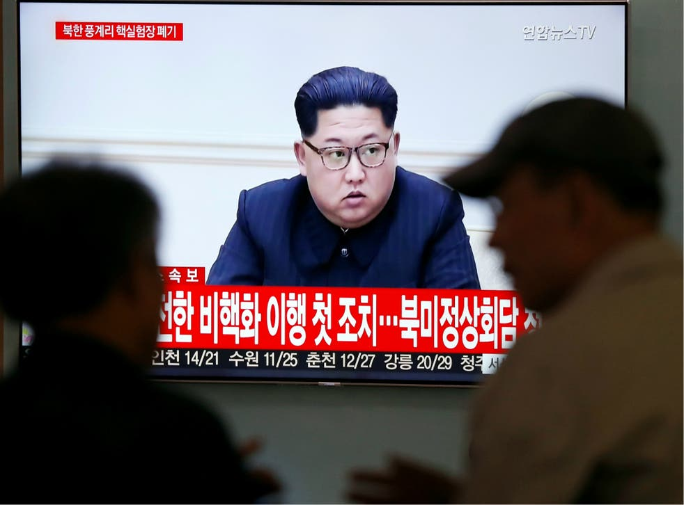 People watch a TV broadcasting a news report of North Korean leader Kim Jong-un, in Seoul, South Korea, 24 May 2018.