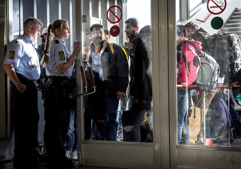 police guide a group of migrants as they arrive in rodby denmark - 12 Ghetto Days Of Christmas