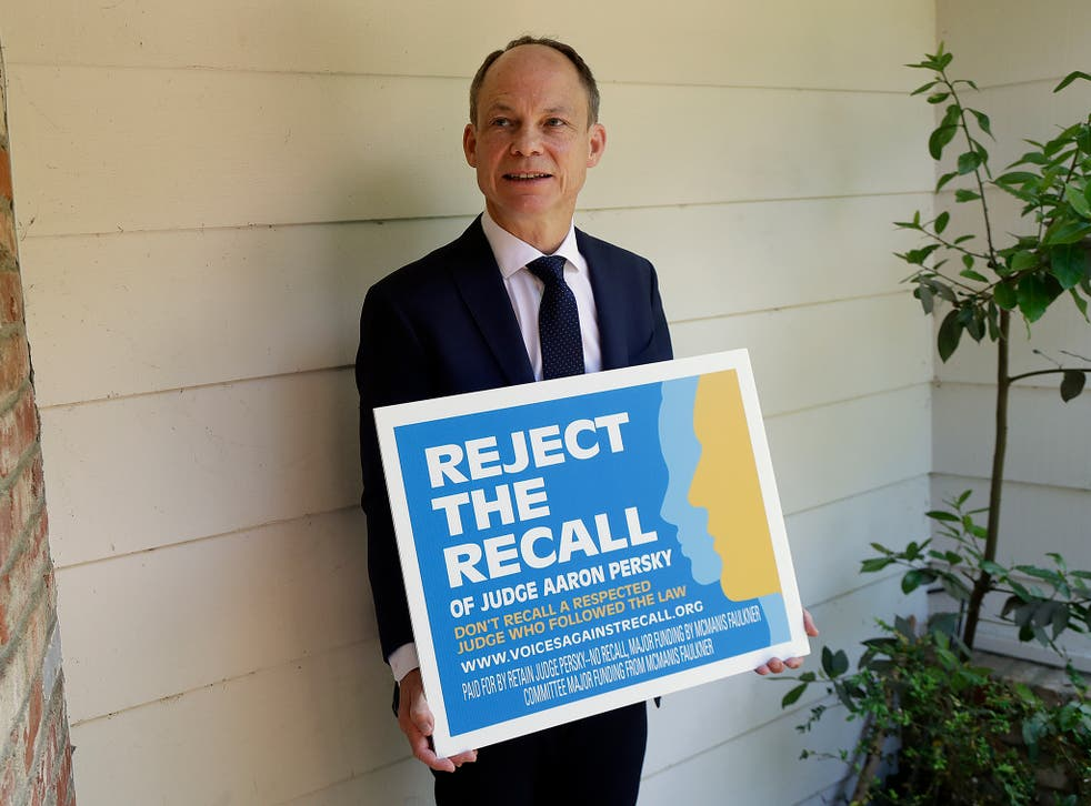 Judge Aaron Persky poses for a photo with a sign opposing his recall in Los Altos Hills, California