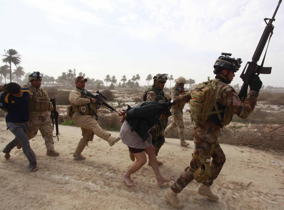 Members of the Iraqi security forces arrest a suspected Isis fighter in Jurf al Sakhar, 15 February 2014